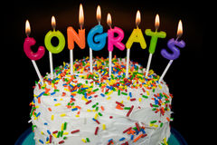 Congrats candles on layered cake. Glowing congrats candle on cake with colorful candy sprinkles stock photos