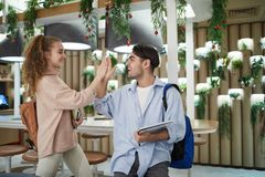 Congrats. Two ecstatic teenagers in casualwear giving high five to each other while spending time in college cafe stock images