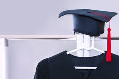 Congratulate graduate.Graduation gown and black hat stock images