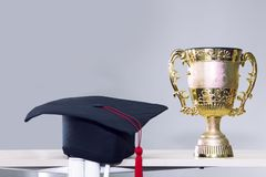 Congratulate graduate.Trophy and black hat on background. stock image