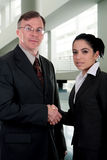 Congratulation. Businessmen and businesswomen exchanging an handshake stock photo