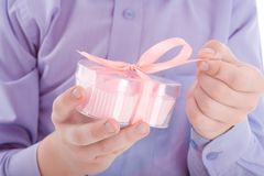 Congratulation! Boy open a gift in a pink box Stock Photography