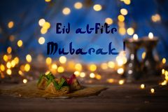 Congratulation: Eid al-Fitr Mubarak! Arabic sweets on a wooden s. Urface. Candle holders, night light and night blue sky with crescent moon in the background Stock Images
