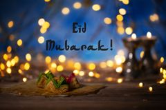 Congratulation: Eid Mubarak! Arabic sweets on a wooden surface. Candle holders, night light and night blue sky with crescent moon in the background Stock Image
