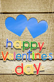 Congratulation with Happy Valentines Day  and two holes as hearts in wooden planks Royalty Free Stock Photography