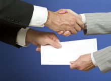 Congratulations!. Two people shaking hands and exchanging a white envelope with available copy space for adding text Royalty Free Stock Image