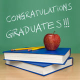 Congratulations graduates. Written on a chalkboard. Books, pencils and an apple on foreground Stock Photos