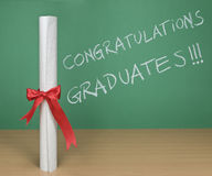 Congratulations graduates. Written on a chalkboard with a diploma on forefround Stock Photography
