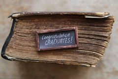 Congratulations graduates text and vintage book on old table Stock Images