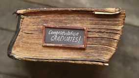 Congratulations graduates text and vintage book on table stock video