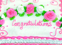 Congratulations. In iced writing decorates frosted white cake.  Roses in pink and white sit in swirls amid green leaves.  Mounds of white frosting leaves room Stock Photos