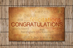 Congratulations. In many languages over classic stone and bamboo Royalty Free Stock Images