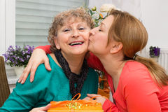 Congratulations. Mother is kissed by her daughter Stock Images