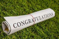 Congratulations newspaper. On green meadow Stock Photos