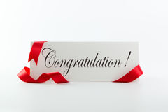 Congratulations note or greeting card. With red ribbon over white background Royalty Free Stock Photography