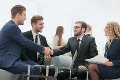 Congratulations! Two cheerful businessmen shaking hands while be Stock Photo