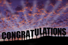 Congratulations. The word congratulations on a hillside silhouetted with puffy clouds Royalty Free Stock Photo