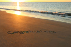 Congratulations. Written in sand on the beach during sunrise Stock Images