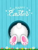 Congratulatory Easter card with a hand-written inscription Happy Easter and a white fluffy rabbit from below in a hole against the stock illustration