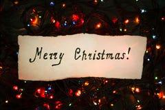 Congratulatory inscription merry Christmas on a Christmas garlan Stock Photos