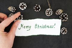 Congratulatory inscription merry Christmas on white paper. In his hands, on a dark background Royalty Free Stock Image