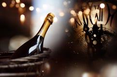 Congratulazioni con un champagne e un orologio della bottiglia per il nuovo anno fotografia stock libera da diritti