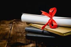Congratulazioni per laurearsi il tocco e la graduazione fanno scorrere, legato con il nastro rosso, su una pila di vecchio libro  Immagine Stock Libera da Diritti