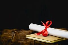 Congratulazioni per laurearsi il tocco e la graduazione fanno scorrere, legato con il nastro rosso, su una pila di vecchio libro  Fotografie Stock