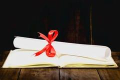 Congratulazioni per laurearsi il tocco e la graduazione fanno scorrere, legato con il nastro rosso, su una pila di vecchio libro  Fotografia Stock