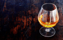 Conhaque de incandescência em um vidro elegante do copo de conhaque Fotos de Stock