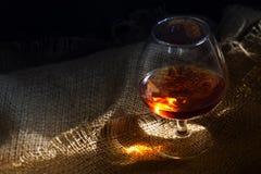 Conhaque ou aguardente em um vidro com um reflexo claro de incandescência no rusti Imagens de Stock Royalty Free