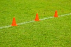 Coni arancio sul campo verde di calcio o di calcio del tappeto erboso, attrezzatura di addestramento Fotografie Stock Libere da Diritti