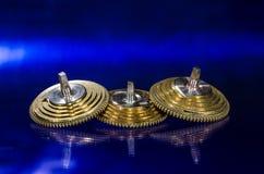 Coni d'annata del Fusee dell'orologio da tasca che riposano su una superficie blu Fotografie Stock