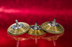 Coni d'annata del Fusee dell'orologio da tasca che riposano su una superficie rossa Immagine Stock