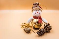 Coni del giocattolo e di abete del pupazzo di neve di Natale su un fondo beige fotografia stock