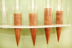 Coni della cialda del gelato sull'erogatore Le cornette del gelato hanno imballato in erogatore sulla parete del deposito Negozio Immagine Stock Libera da Diritti