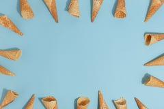 Coni della cialda per il gelato su un fondo blu Vista superiore immagini stock libere da diritti