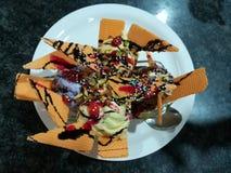 Coni di gelato della fragola, del cioccolato, della vaniglia e del pistacchio sopra priorità bassa bianca fotografia stock
