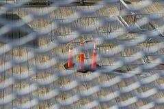 Coni di traffico su un pavimento di legno slated, visto attraverso una griglia del metallo bianco fotografia stock