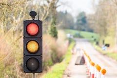 Coni gialli rossi dei semafori di lavori stradali BRITANNICI dell'autostrada Immagine Stock