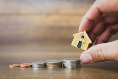Coni il modello della casa e dei soldi su fondo di legno Fotografia Stock