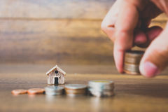 Coni il modello della casa e dei soldi su fondo di legno Fotografia Stock Libera da Diritti