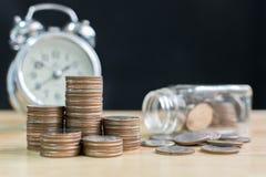 Coni la pila con il fondo vago del barattolo e dell'orologio, finanza e dentro Fotografie Stock Libere da Diritti