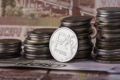 Coni la rublo sui precedenti delle banconote e delle pile dei soldi Immagine Stock