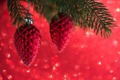 Coni rossi delle decorazioni di natale sull'albero di natale sul fondo rosso del bokeh di scintillio Fotografia Stock