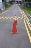 Coni rossi e strada d'avvertimento a strisce gialla fotografia stock libera da diritti