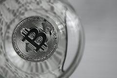 Conia i bitcoins in un vetro di vino, primo piano Fotografia Stock
