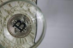 Conia i bitcoins in un vetro di vino, primo piano Fotografie Stock
