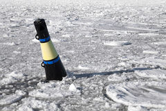 Conical black and yellow buoy on frozen sea Royalty Free Stock Image