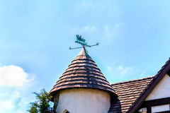 Conical slat roof and winvane. Conical slat roof with charming patinated brass vane and blue sky with clouds Stock Photography